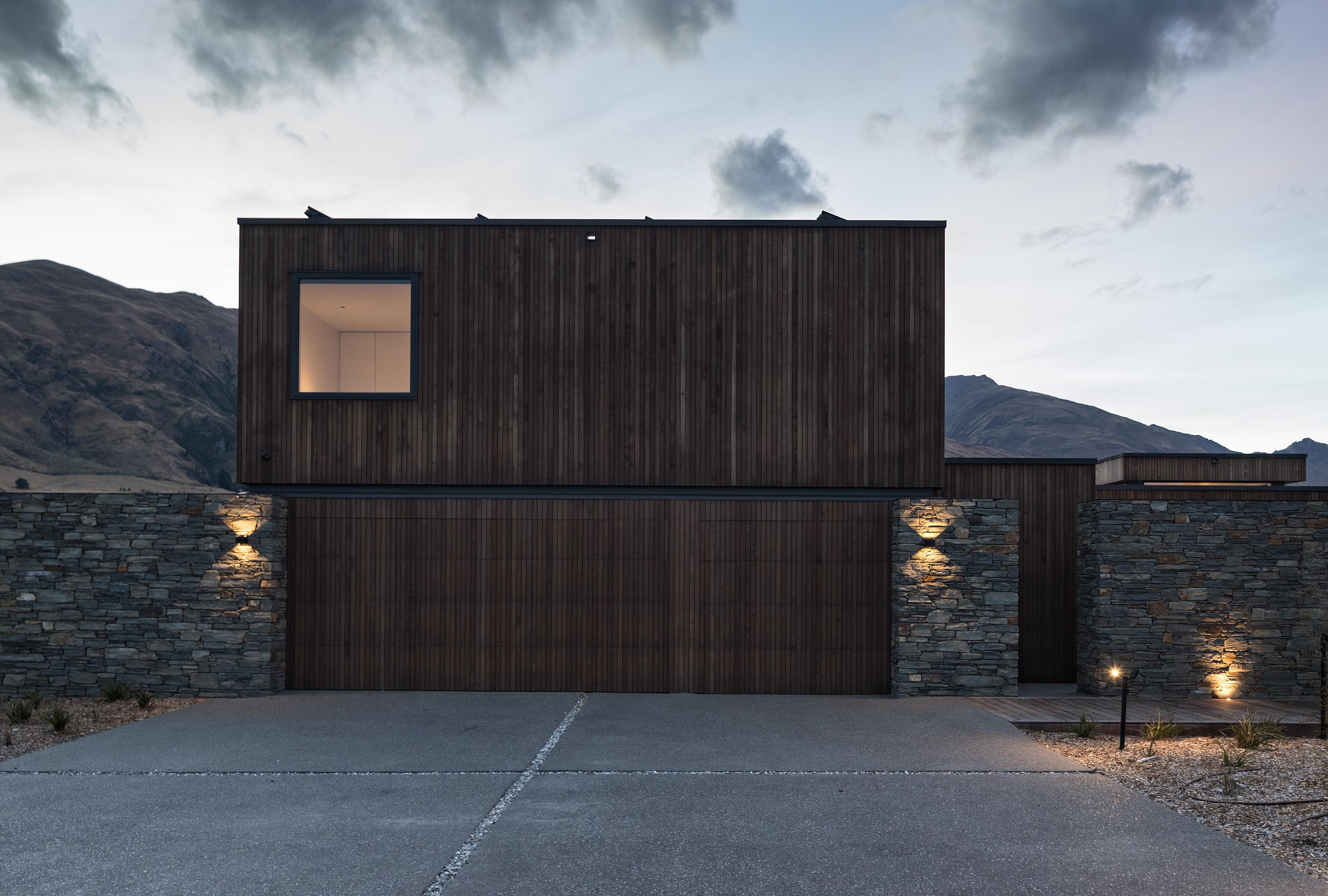 Rear of the house, showcasing local stone, sympathetic timber, and contemporary box-like form