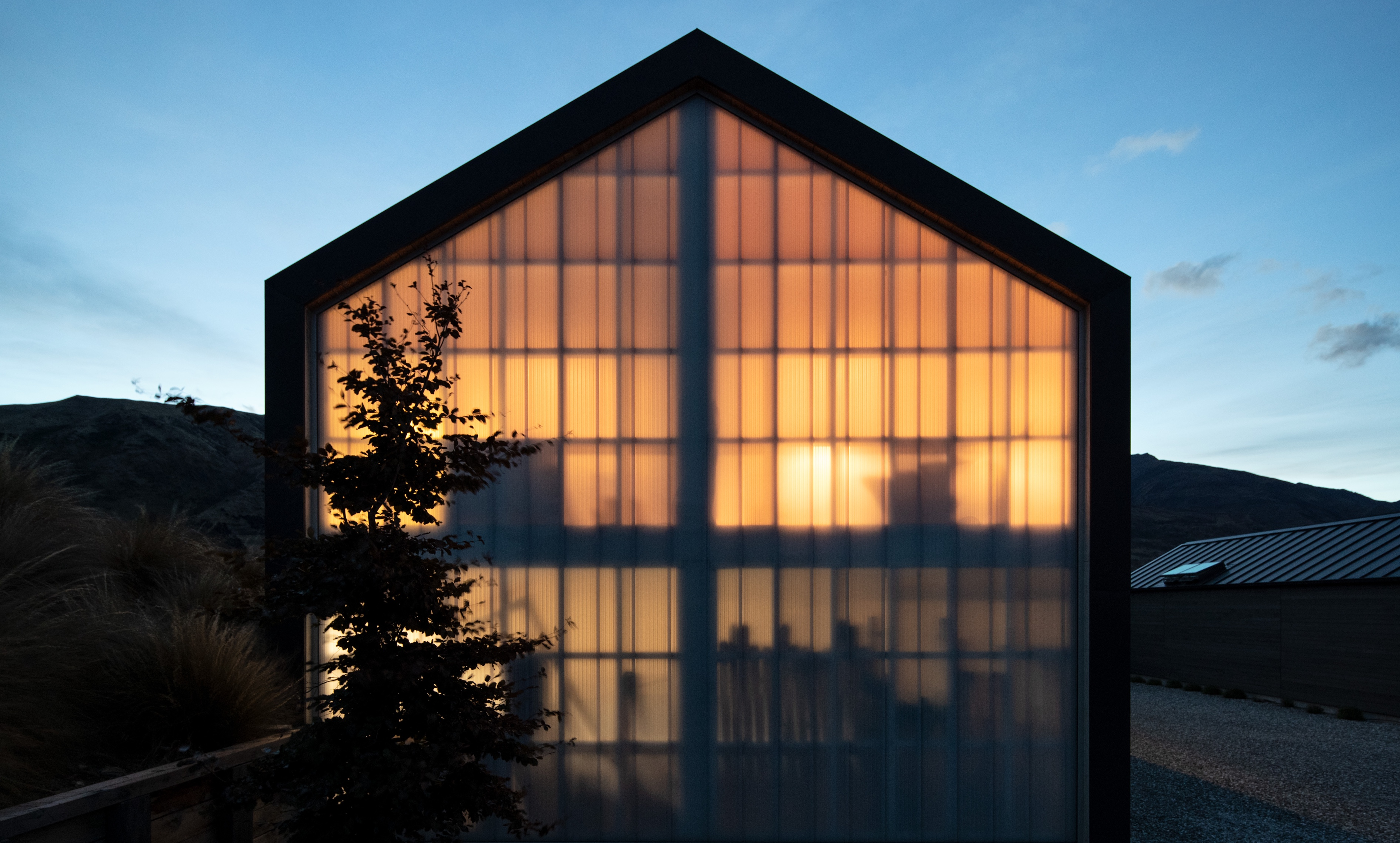 Exterior of Westmeadows Shed at night, with light shining through floor-to-sealing translucent polycarbonate