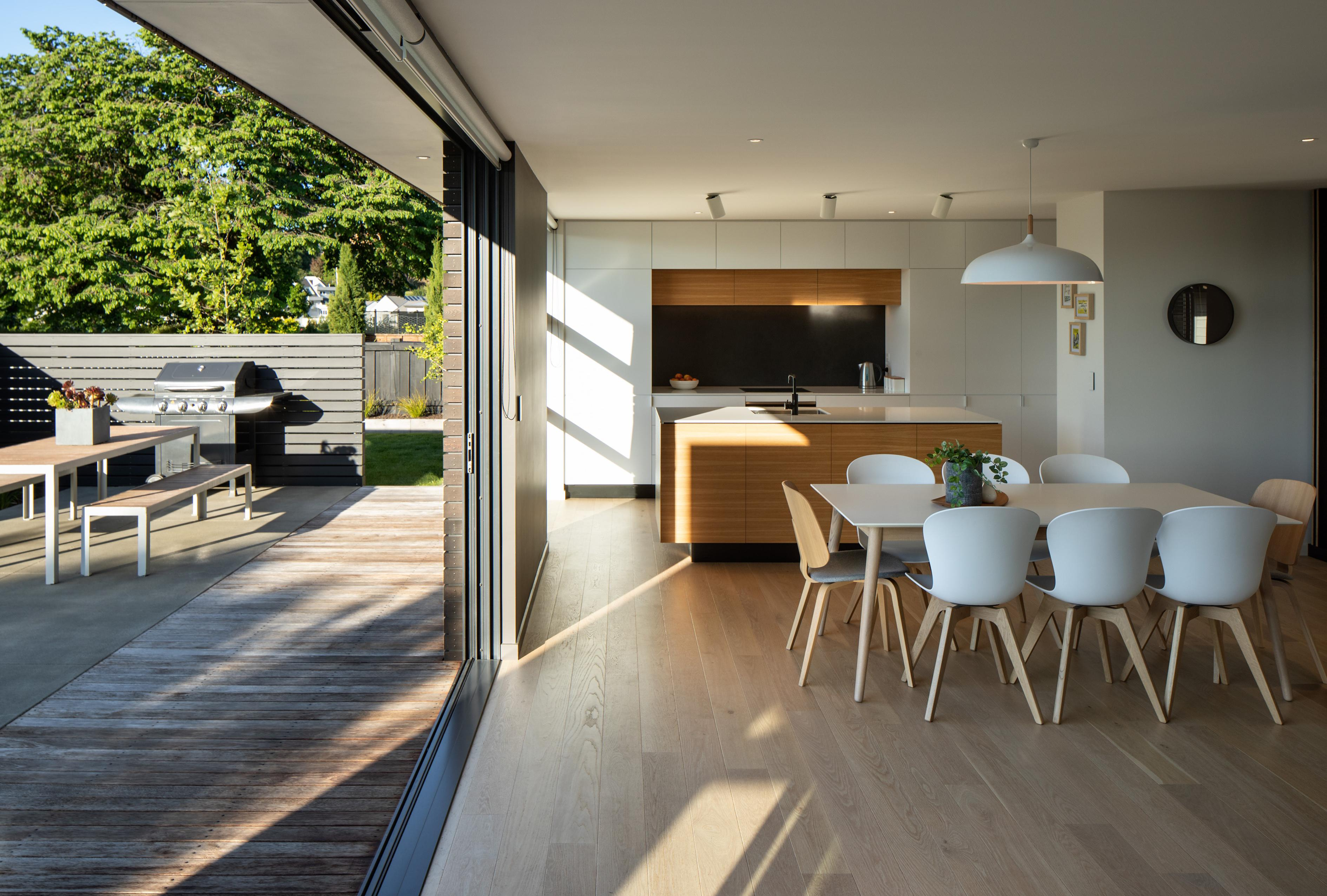 Interior of the kitchen and dining area, with sliding door opened to an outdoor living area with seating and barbecue