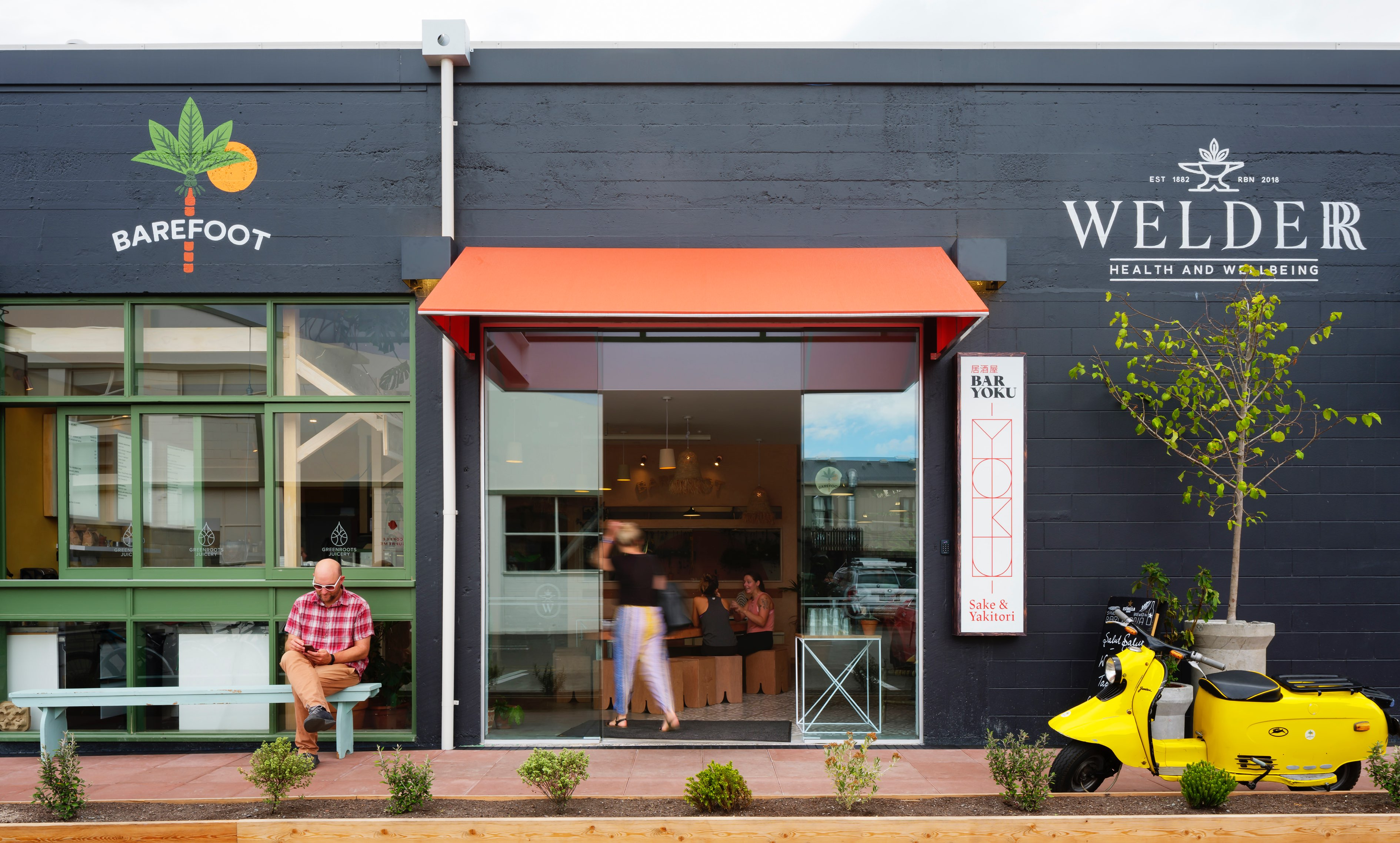 Exterior of The Welder with patrons inside at Greenroots Juicery